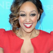 Tia Mowry graces the red carpet smiling with her red lips.