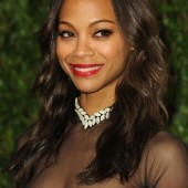 Zoe Saldana shows off her red lips with a smile on the red carpet.